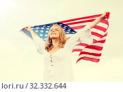 happy young woman with american flag outdoors. Стоковое фото, фотограф Syda Productions / Фотобанк Лори