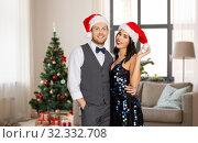 Купить «happy couple in santa hats at home on christmas», фото № 32332708, снято 15 декабря 2017 г. (c) Syda Productions / Фотобанк Лори
