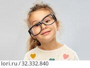 Купить «smiling little girl in crookedly placed glasses», фото № 32332840, снято 28 сентября 2019 г. (c) Syda Productions / Фотобанк Лори
