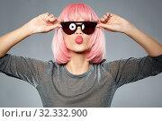 Купить «woman in pink wig and sunglasses sending air kiss», фото № 32332900, снято 30 сентября 2019 г. (c) Syda Productions / Фотобанк Лори