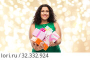 Купить «happy woman holding gift boxes over lights», фото № 32332924, снято 15 сентября 2019 г. (c) Syda Productions / Фотобанк Лори