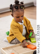 Купить «african baby girl playing with toy blocks at home», фото № 32333028, снято 29 сентября 2019 г. (c) Syda Productions / Фотобанк Лори