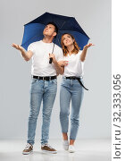 Купить «happy couple in white t-shirts with umbrella», фото № 32333056, снято 6 октября 2019 г. (c) Syda Productions / Фотобанк Лори
