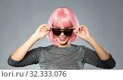 Купить «happy woman in pink wig and black sunglasses», фото № 32333076, снято 30 сентября 2019 г. (c) Syda Productions / Фотобанк Лори