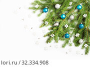 Christmas tree branches decorated with blue and silver balls and white snowflakes, on white background. Стоковое фото, фотограф Юлия Бабкина / Фотобанк Лори