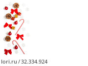 Border of Christmas decorations from snowflakes, candy canes, bows and pine cones on white background. Стоковое фото, фотограф Юлия Бабкина / Фотобанк Лори