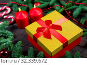Купить «Gift with a red ribbon, burning candles and green branches of spruce on a wooden table», фото № 32339672, снято 30 декабря 2018 г. (c) Константин Лабунский / Фотобанк Лори