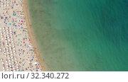Купить «Picturesque overview of ocean shoreline with colored umbrellas of vacationers on sandy beach», видеоролик № 32340272, снято 7 июля 2019 г. (c) Яков Филимонов / Фотобанк Лори