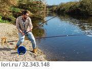Купить «Adult man standing near river and pulling fish expressing emotions of dedication», фото № 32343148, снято 15 марта 2019 г. (c) Яков Филимонов / Фотобанк Лори