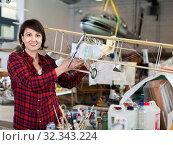 Купить «Smiling woman showing sports biplane model she created in aircraft workshop», фото № 32343224, снято 4 марта 2019 г. (c) Яков Филимонов / Фотобанк Лори