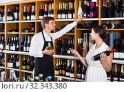 Купить «portrait of male seller showing bottle of wine to female customer in wine shop», фото № 32343380, снято 10 декабря 2019 г. (c) Яков Филимонов / Фотобанк Лори