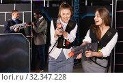 Купить «Emotional portrait of two women holding laser pistols and playing laser tag with colleagues», фото № 32347228, снято 4 апреля 2019 г. (c) Яков Филимонов / Фотобанк Лори