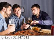 Купить «friends looking at phone while drinking beer», фото № 32347312, снято 10 января 2018 г. (c) Яков Филимонов / Фотобанк Лори