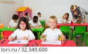 Купить «Portrait of schoolgirl and schoolboy at desk», фото № 32349600, снято 15 ноября 2018 г. (c) Яков Филимонов / Фотобанк Лори