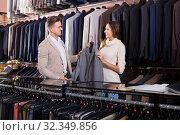 Купить «happy female seller demonstrating men's shirts to customer», фото № 32349856, снято 20 февраля 2020 г. (c) Яков Филимонов / Фотобанк Лори