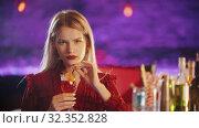 Купить «Gorgeous young woman sitting by the bartender stand - drinking a beverage from the straw and looking in the camera», видеоролик № 32352828, снято 19 февраля 2020 г. (c) Константин Шишкин / Фотобанк Лори