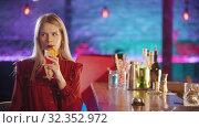 Купить «Gorgeous blonde young woman with red lipstick sitting by the bartender stand - drinking a red beverage from the straw», видеоролик № 32352972, снято 19 февраля 2020 г. (c) Константин Шишкин / Фотобанк Лори