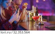 Купить «Young woman sitting by the bartender stand and using her phone - taking a photo of the drink», видеоролик № 32353564, снято 19 февраля 2020 г. (c) Константин Шишкин / Фотобанк Лори