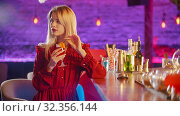 Gorgeous young woman sitting by the bartender stand - drinking with a the straw and looking to the side. Стоковое фото, фотограф Константин Шишкин / Фотобанк Лори