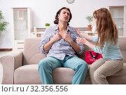 Купить «Young couple in first aid concept at home», фото № 32356556, снято 10 мая 2019 г. (c) Elnur / Фотобанк Лори