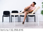 Купить «Young injured man waiting for his turn in hospital hall», фото № 32356616, снято 3 мая 2019 г. (c) Elnur / Фотобанк Лори