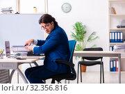 Купить «Young businessman sitting and working in the office», фото № 32356816, снято 18 марта 2019 г. (c) Elnur / Фотобанк Лори
