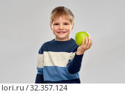 Купить «little boy in striped pullover with green apple», фото № 32357124, снято 28 сентября 2019 г. (c) Syda Productions / Фотобанк Лори