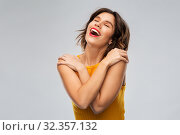 happy grateful young woman in mustard yellow top. Стоковое фото, фотограф Syda Productions / Фотобанк Лори
