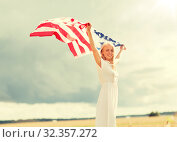 happy woman with american flag on cereal field. Стоковое фото, фотограф Syda Productions / Фотобанк Лори