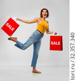 Купить «happy smiling young woman with shopping bags», фото № 32357340, снято 30 сентября 2019 г. (c) Syda Productions / Фотобанк Лори