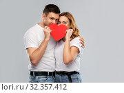 Купить «smiling couple hiding behind big red heart», фото № 32357412, снято 6 октября 2019 г. (c) Syda Productions / Фотобанк Лори