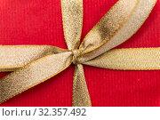 Купить «close up of christmas red gift box with golden bow», фото № 32357492, снято 11 декабря 2018 г. (c) Syda Productions / Фотобанк Лори