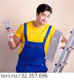 Купить «Young contractor employee applying plaster on wall», фото № 32357696, снято 15 марта 2018 г. (c) Elnur / Фотобанк Лори