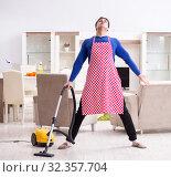 Купить «Young man vacuum cleaning his apartment», фото № 32357704, снято 13 марта 2018 г. (c) Elnur / Фотобанк Лори