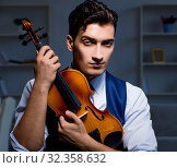Купить «Young musician man practicing playing violin at home», фото № 32358632, снято 15 августа 2017 г. (c) Elnur / Фотобанк Лори