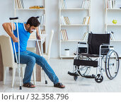 Купить «Young man recovering after surgery at home with crutches and a w», фото № 32358796, снято 26 июля 2017 г. (c) Elnur / Фотобанк Лори