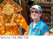 Купить «Russia, Samara, July 2019: An attractive mature woman stands near a tray with curly baked goods at a gastronomic festival.», фото № 32366132, снято 27 июля 2019 г. (c) Акиньшин Владимир / Фотобанк Лори