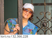 An attractive mature woman peeks out from behind a forged gate. Стоковое фото, фотограф Акиньшин Владимир / Фотобанк Лори