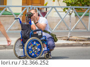 Russia, Samara, July 2019: Little sick disabled child in a wheelchair surrounded by father on a city street. Редакционное фото, фотограф Акиньшин Владимир / Фотобанк Лори