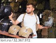 Купить «Man choosing helmet», фото № 32367972, снято 4 июля 2017 г. (c) Яков Филимонов / Фотобанк Лори