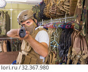 Купить «adult guy in military equipment with weapon in army shop», фото № 32367980, снято 4 июля 2017 г. (c) Яков Филимонов / Фотобанк Лори