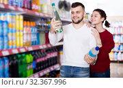 Купить «Young family purchasing soft dinks», фото № 32367996, снято 14 марта 2017 г. (c) Яков Филимонов / Фотобанк Лори