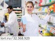 Купить «Adult female looking medicines near shelves», фото № 32368920, снято 28 февраля 2018 г. (c) Яков Филимонов / Фотобанк Лори