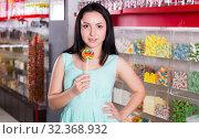 Купить «Smiling girl sucking lollypop in store», фото № 32368932, снято 25 апреля 2017 г. (c) Яков Филимонов / Фотобанк Лори