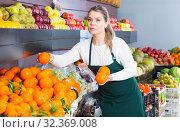 Купить «Positive woman selling fresh oranges and fruits», фото № 32369008, снято 1 апреля 2020 г. (c) Яков Филимонов / Фотобанк Лори