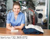 Купить «Worker of laundry writing receipt», фото № 32369072, снято 9 мая 2018 г. (c) Яков Филимонов / Фотобанк Лори