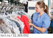 Купить «worker of laundry inspecting clothes after dry cleaning», фото № 32369092, снято 9 мая 2018 г. (c) Яков Филимонов / Фотобанк Лори