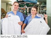 Купить «Two workers showing clean clothing», фото № 32369096, снято 9 мая 2018 г. (c) Яков Филимонов / Фотобанк Лори