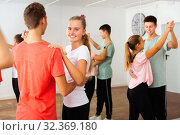 Group of teenage boys and girls training movements of slow foxtrot in dance studio with female coach. Стоковое фото, фотограф Яков Филимонов / Фотобанк Лори