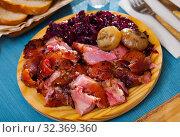 Купить «Pieces of roasted pork knuckle with braised cabbage», фото № 32369360, снято 17 ноября 2019 г. (c) Яков Филимонов / Фотобанк Лори